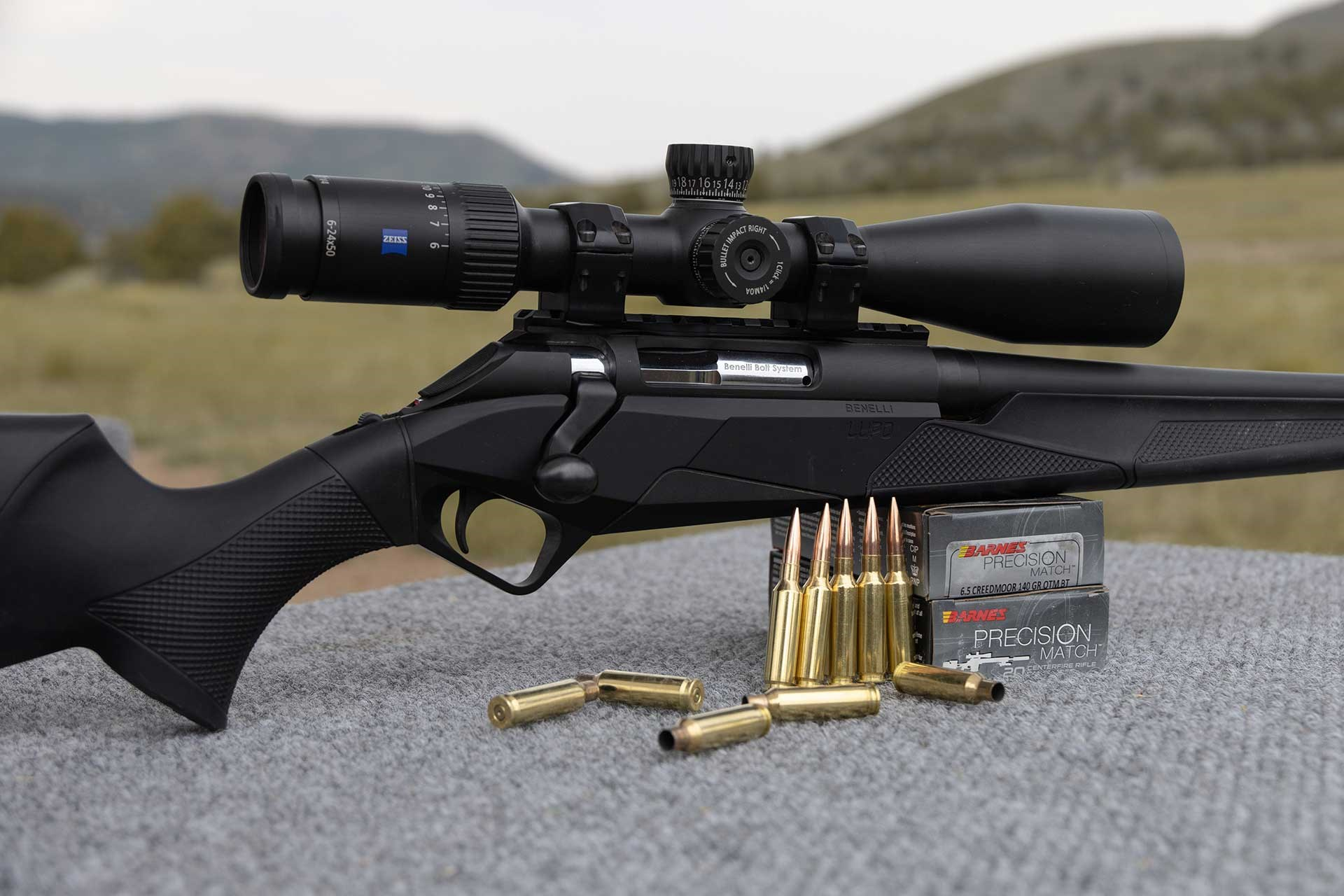 A Benelli Lupo rifle sitting on a shooting bench next to Barnes Precision ammunition.