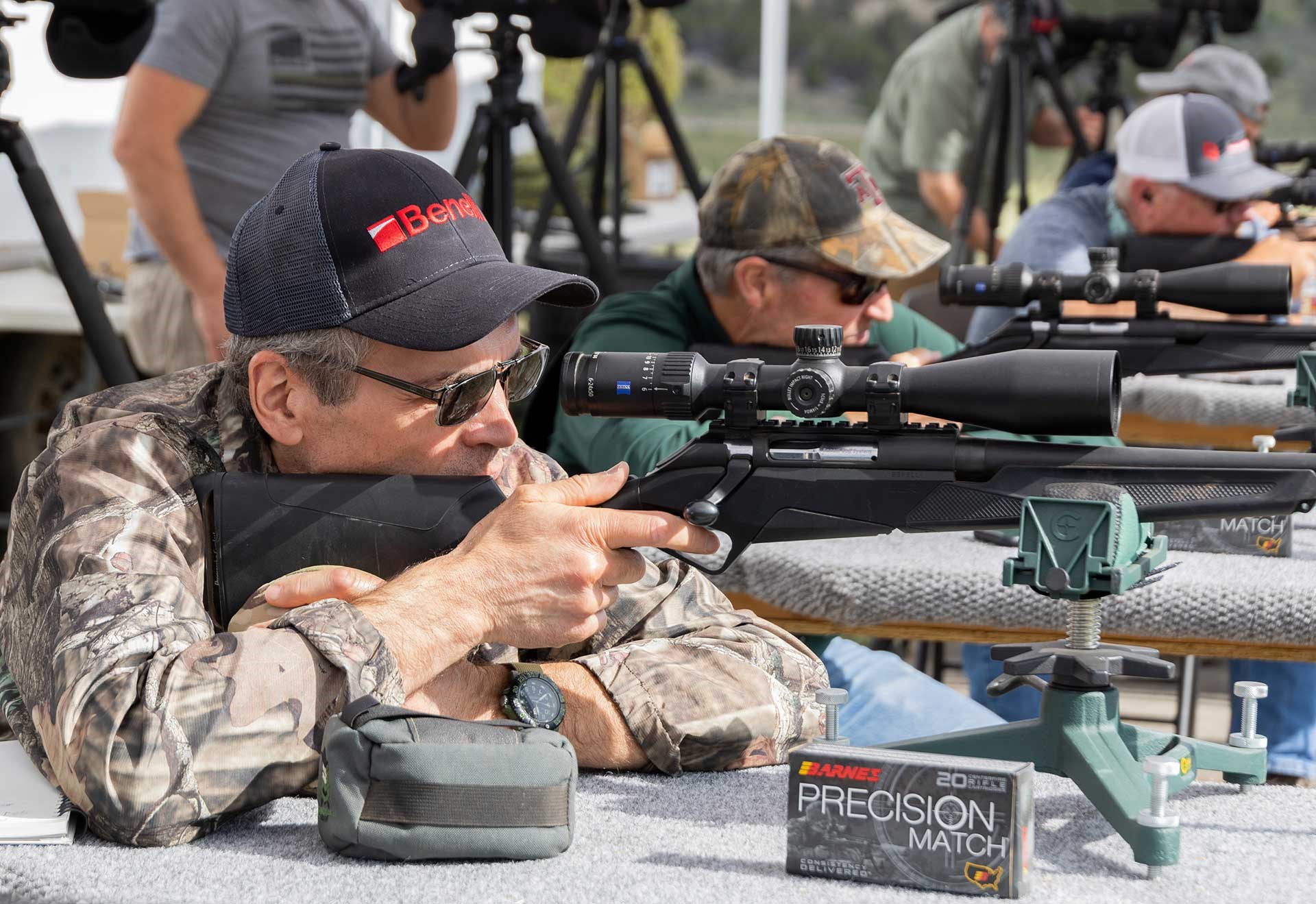 A group of shooters aim their rifles downrange from the bench on a known-distance target range.