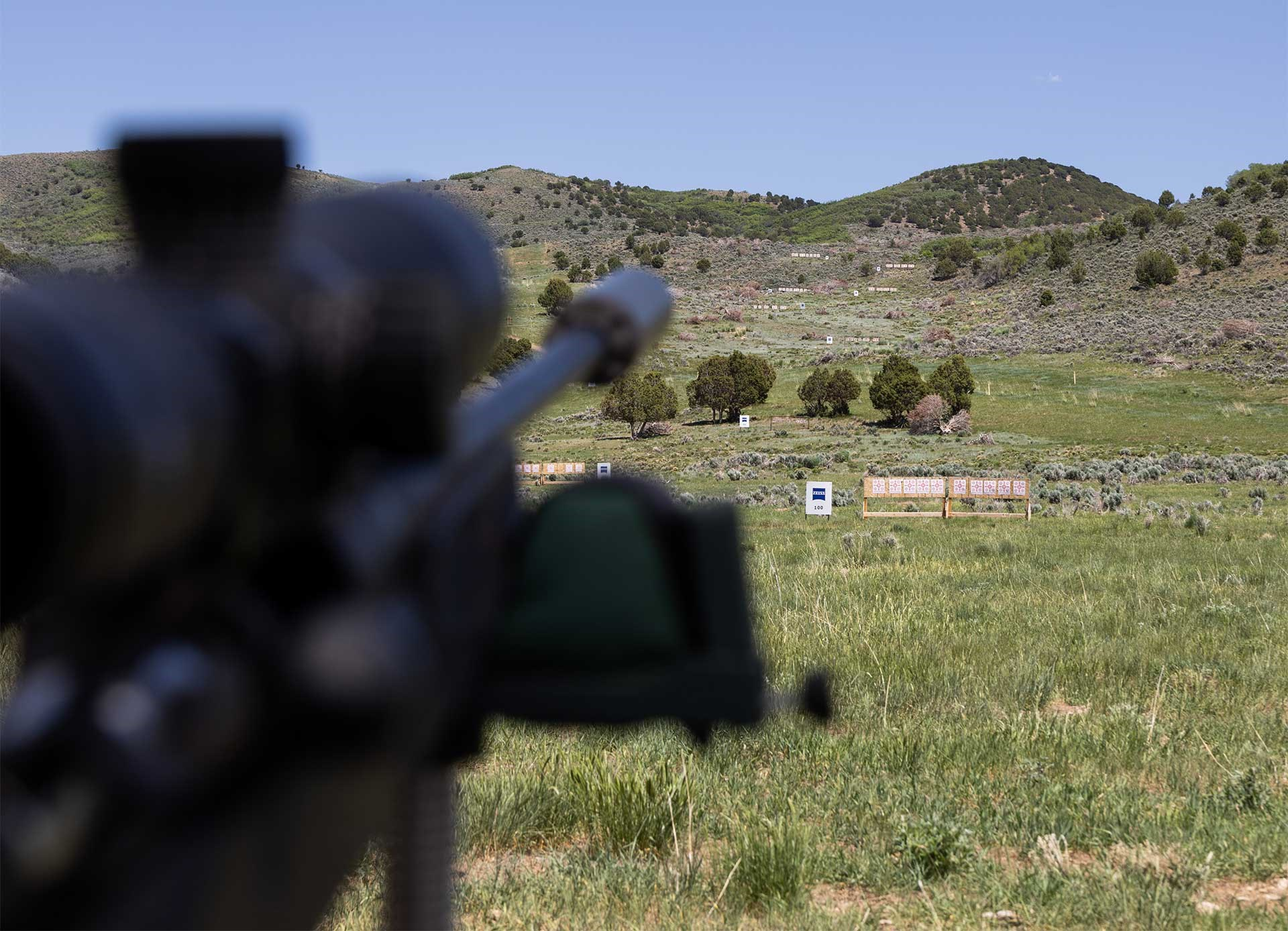 A rifle barrel and scope are seen in the foreground, while targets dot a hillside in the background.