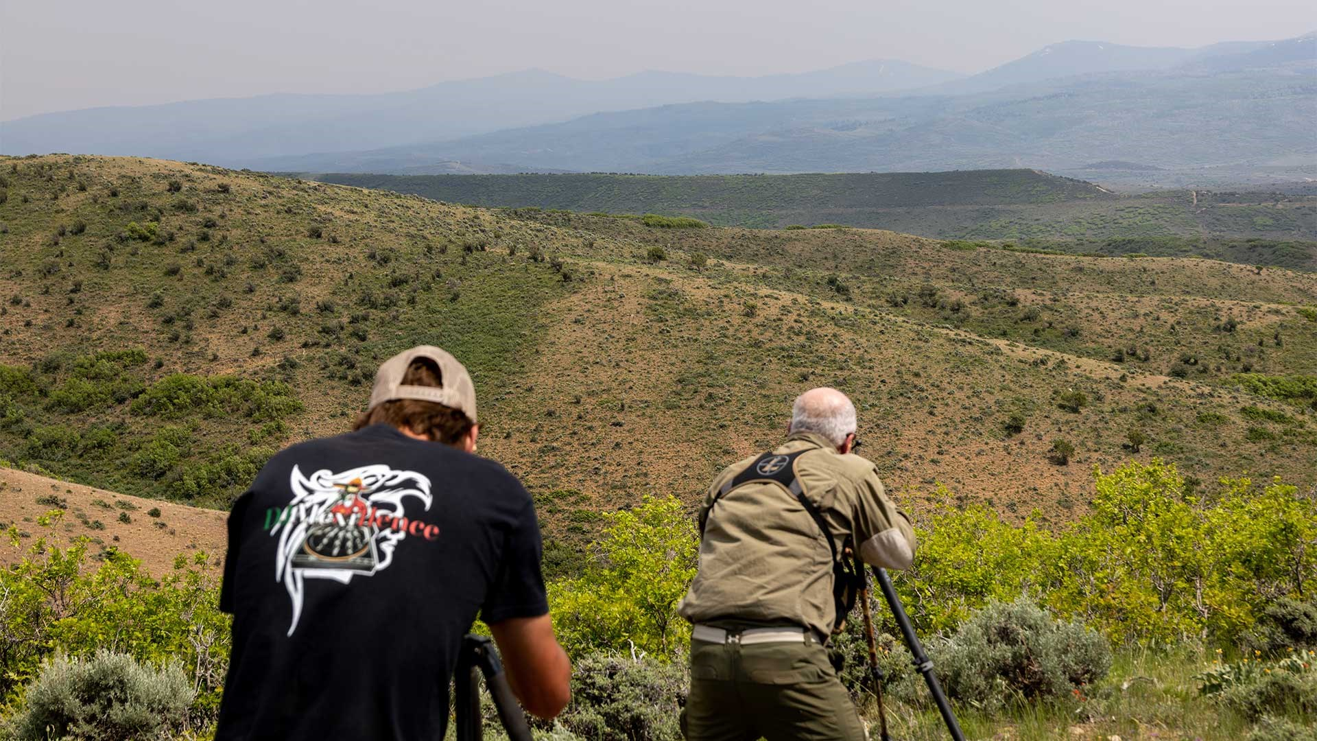 A shooter aims his rifle across mountain ridges while a spotter mounts his spotting scope in the foreground.