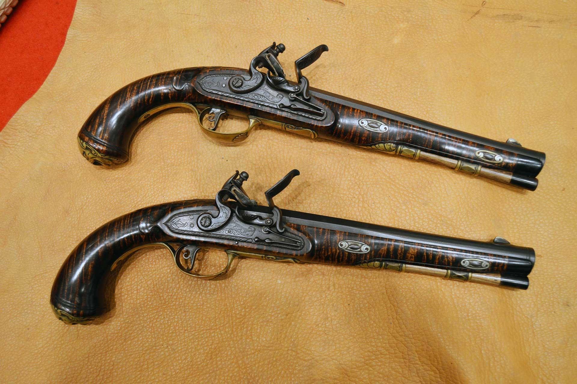 Two flintlock pistols shown on a deerskin background.