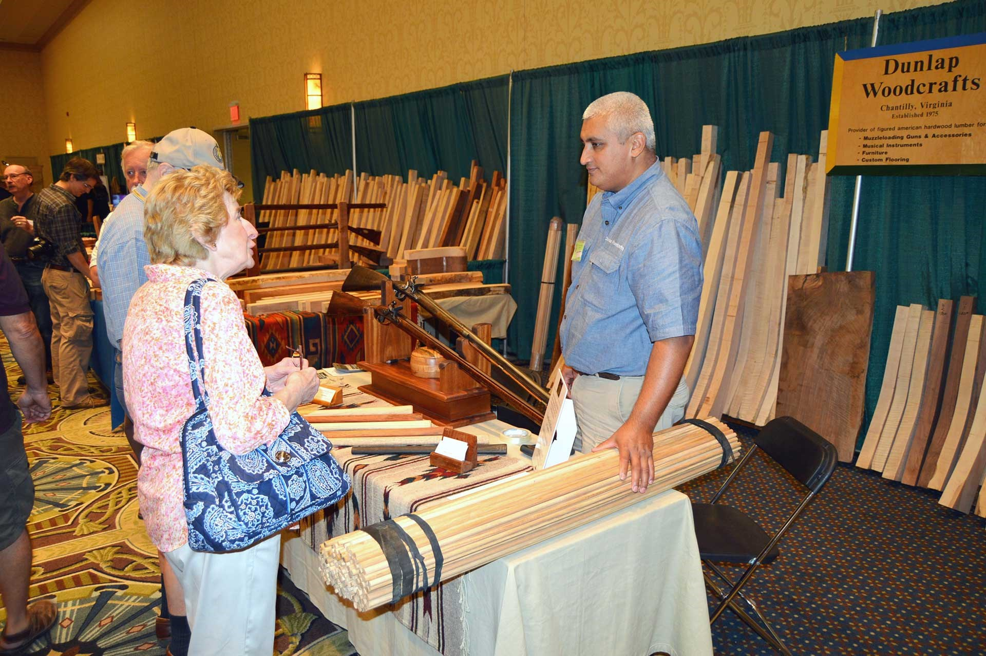 A pile of unfinished rifle stocks lay against the back wall behind a vendor and a woman talking at the CLA Show.