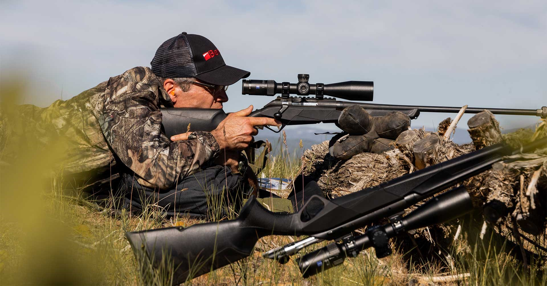 A shooter mounts his Benelli Lupo rifle in the field while shooting off a bag rest.