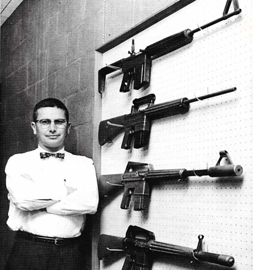man white shirt black pants black rifles wall line row guns carbines engineer