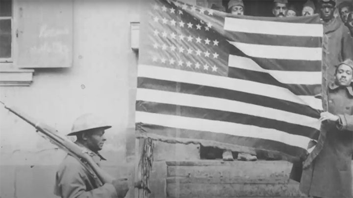 African American soldiers posing with the American flag.