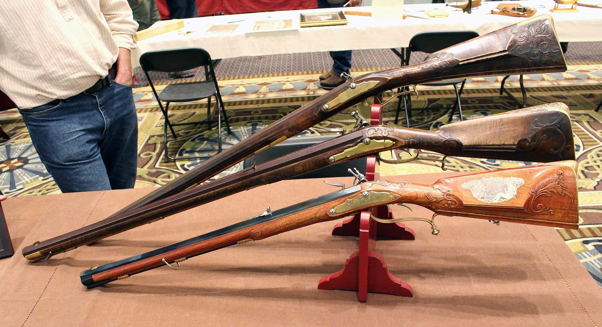 Three short flintlock Jaeger rifles shown on a table at the CLA Show.