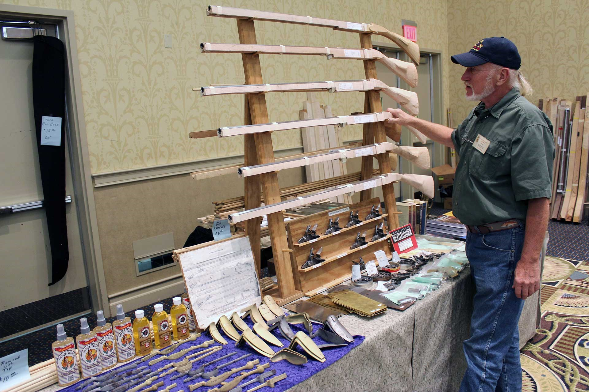 Unfinished flintlock rifle kits displayed at the CLA show are inspected by a show attendee.