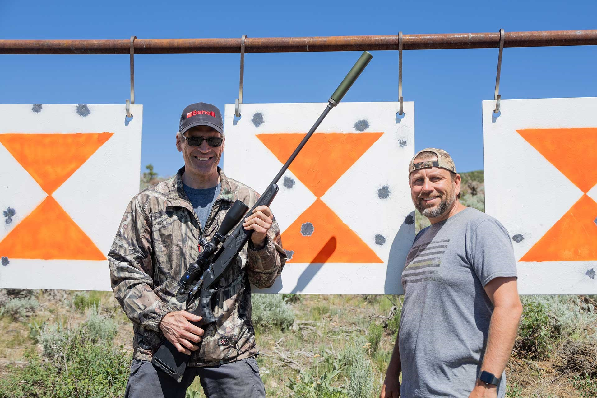 Two men stand next to a steel target showing impact marks. One man is holding a Benelli Lupo rifle with a mounted suppressor.