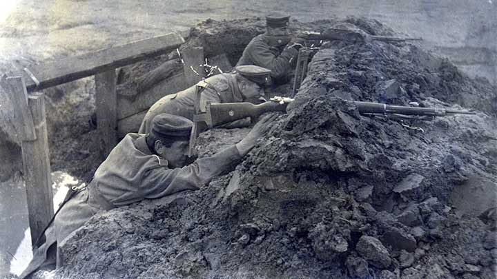 A German soldier takes a look through a pericope across no-man's-land  while a comrade takes aim with a Gew 98.