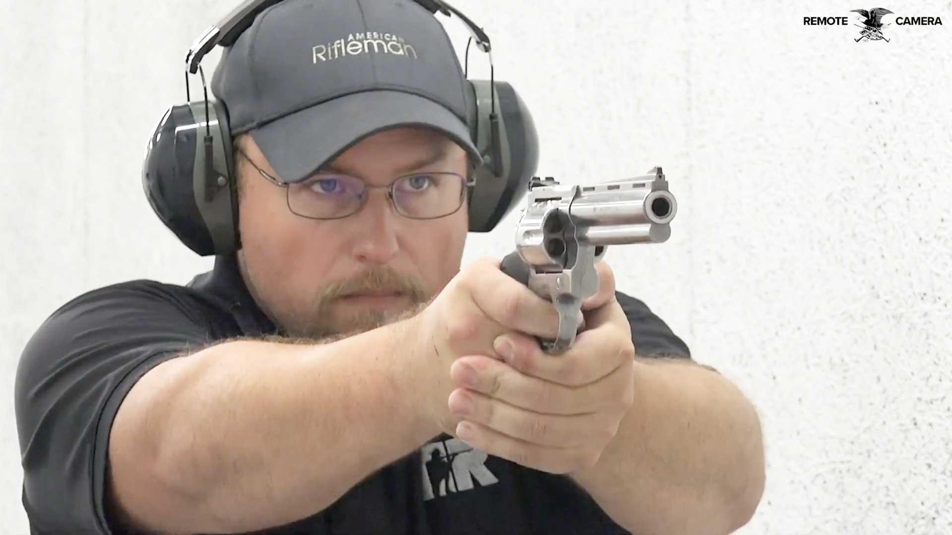 man hat gun earmuffs glasses silver pistol revolver shooting black shirt