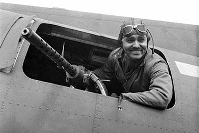 Captain Clark Gable poses with a .50-cal. AN/M2 machine gun