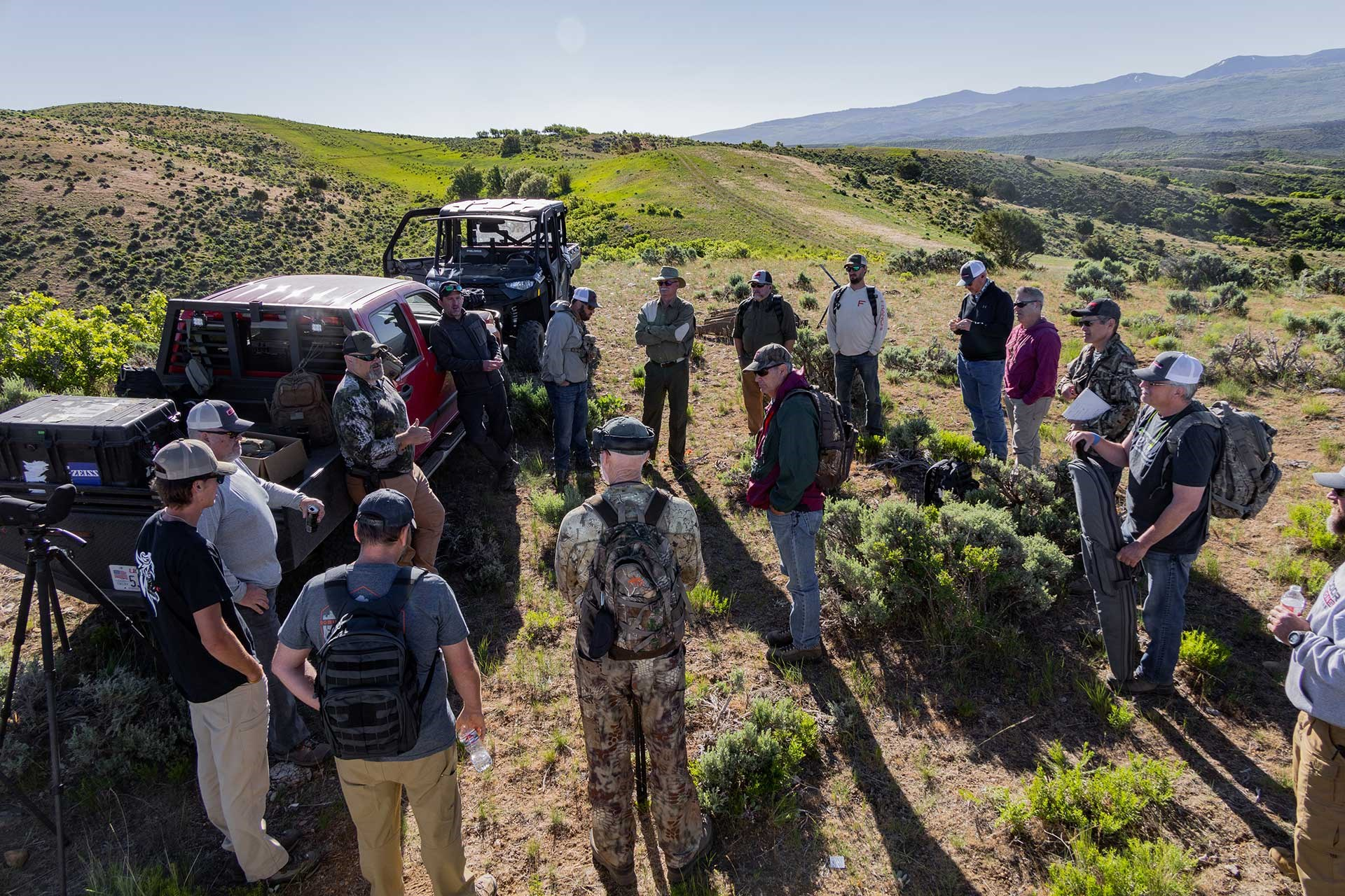 A group of students gathers around trucks in the wilderness at the Outdoor Solutions Long Range School.